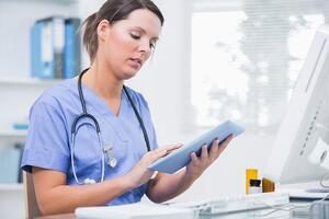 Side view of young female surgeon using digital tablet in front of computer at desk in clinic