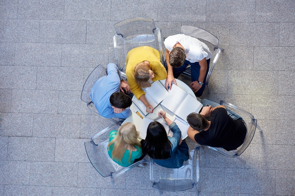top view,  group of students together  at school table working homework and have fun.jpeg